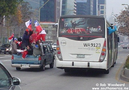 The back of a Ute filled with Chilean football supporters after the victory of Chile over Switzerland in the World Cup. Notice someone hanging out of the bus too.