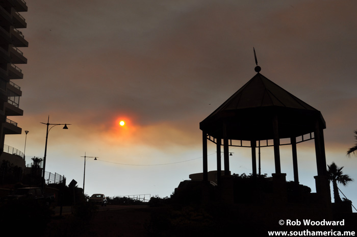 Forest Fire Cloud covering the sun with a conservatory in the foreground