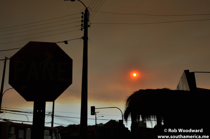 Forest Fire Cloud covering the sun with a darkened stop sign